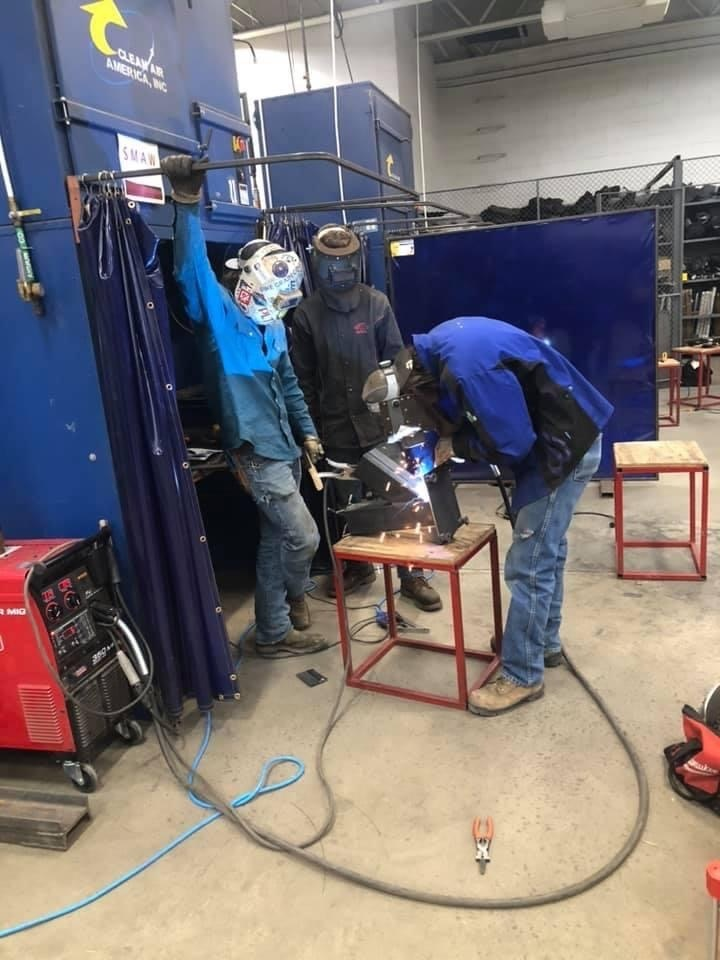 3 welding students working on an project